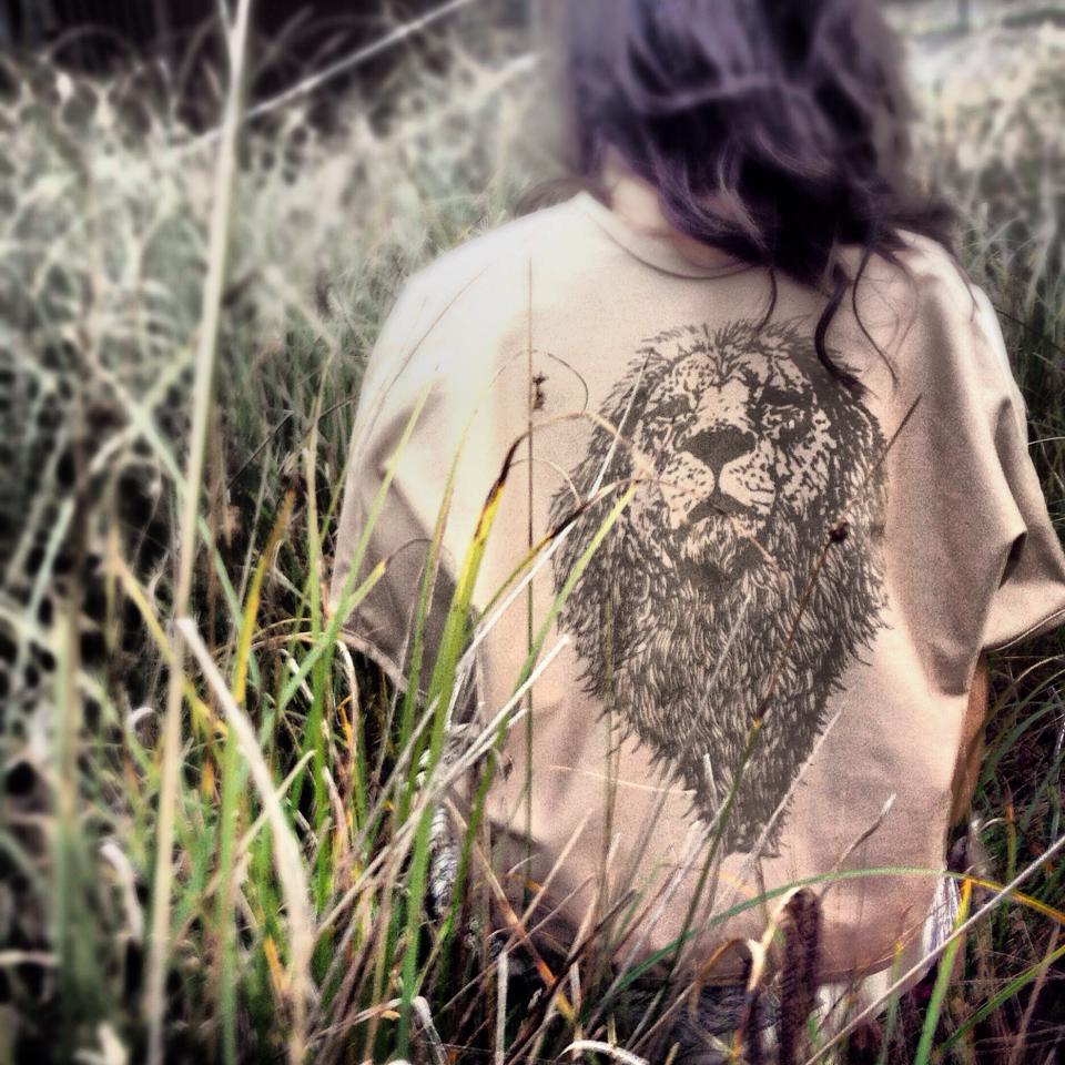 Woman crouching in tall grass wearing lion shirt from The Guardian collection