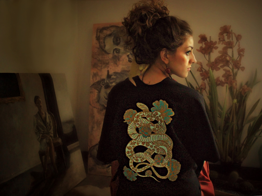 Woman displaying The Toad Frog collection women's black shirt with intricate design