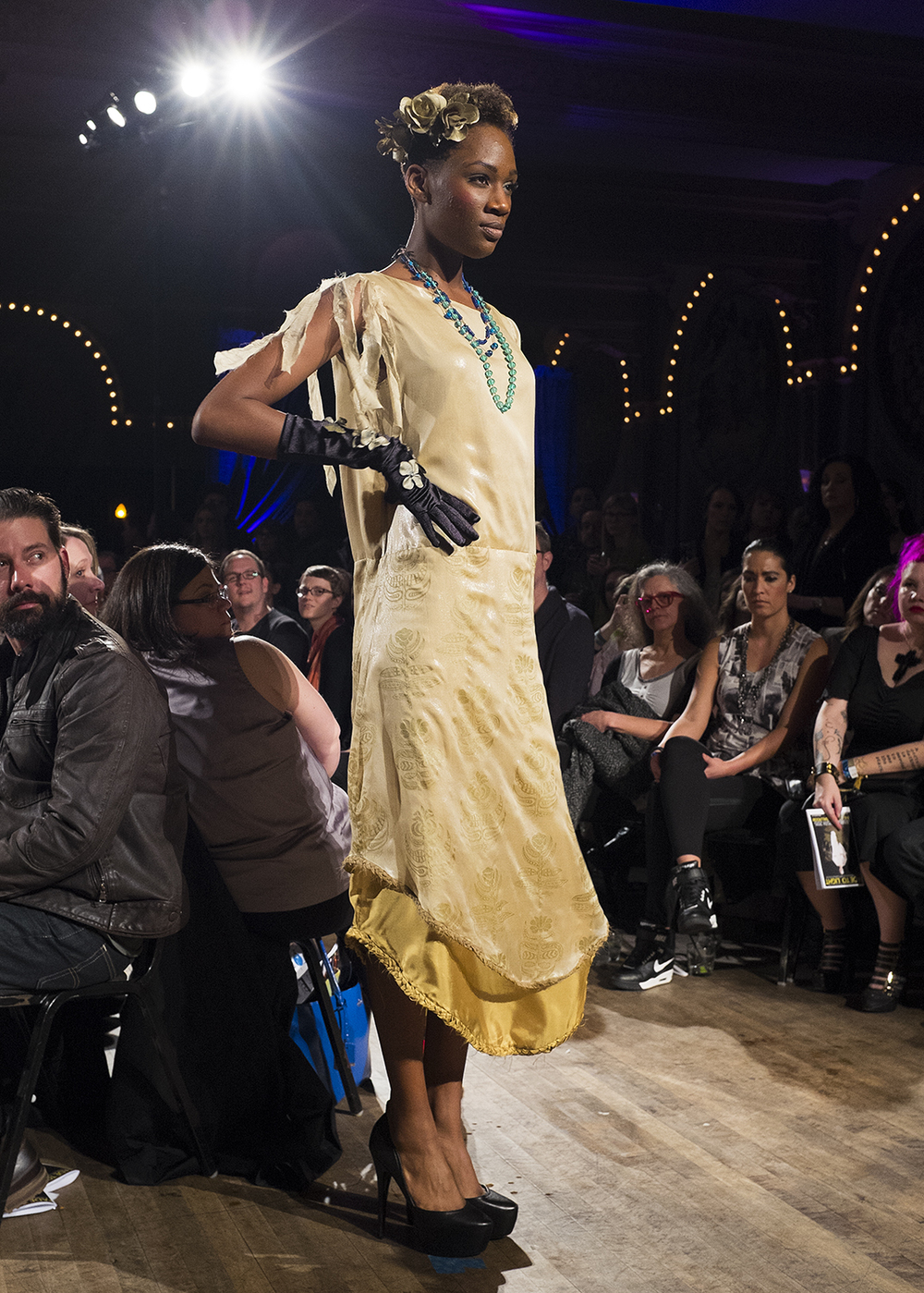 Model walking on runway wearing golden dress
