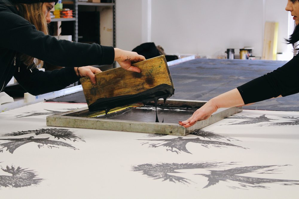 Two workers fill stamp with black ink substance at Veil and Valor studio