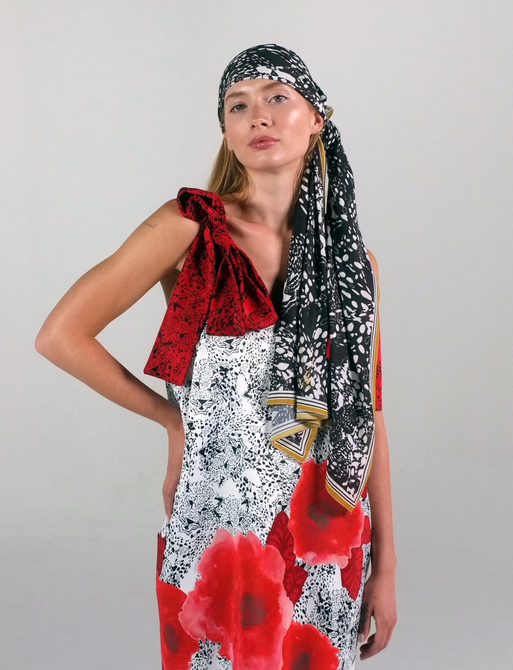 A woman poses with a black and white scarf tied around her head while wearing a red and white floral dress