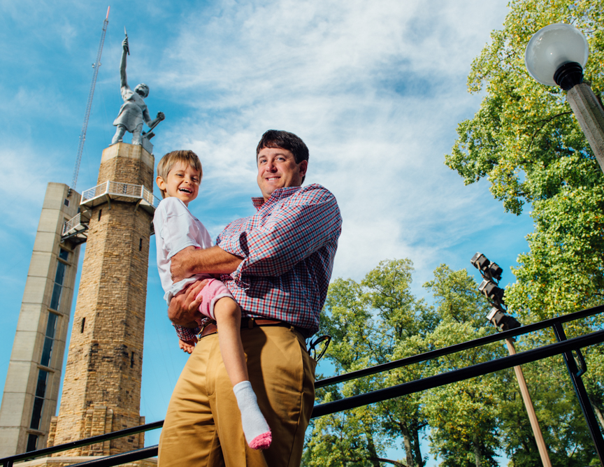 Hud Hudson, founder of Williams-Hudson Inc., and Raylee, 7, stand in front of Vulcan in Downtown Birmingham. Men of Magic Moments calendar 2016. (Photo: Andrea Mabry)