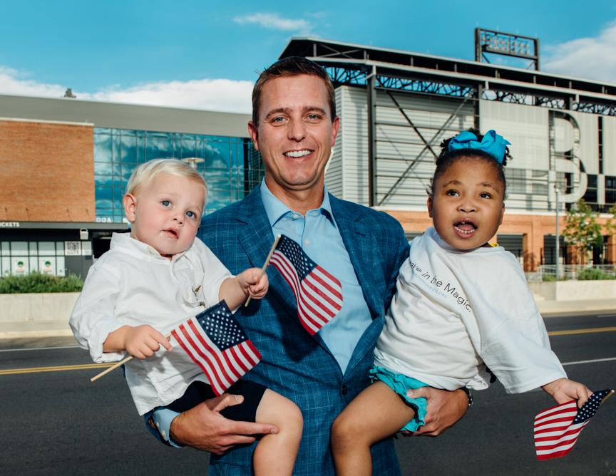 Josh Petty of BB&T of Greater Birmingham holds his son, Jackson, and Cayden, 6, in front of Regions Field in Downtown Birmingham. Men of Magic Moments calendar 2016. (Photo: Andrea Mabry)