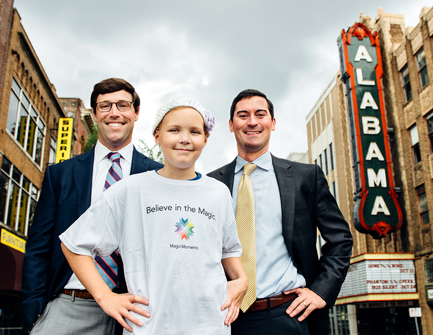 Ron Morrison and Layne Held of ServisFirst Bank stand with Mollie, 13, in front of the Alabama Theatre in Downtown Birmingham. Men of Magic Moments calendar 2016. (Photo: Andrea Mabry)