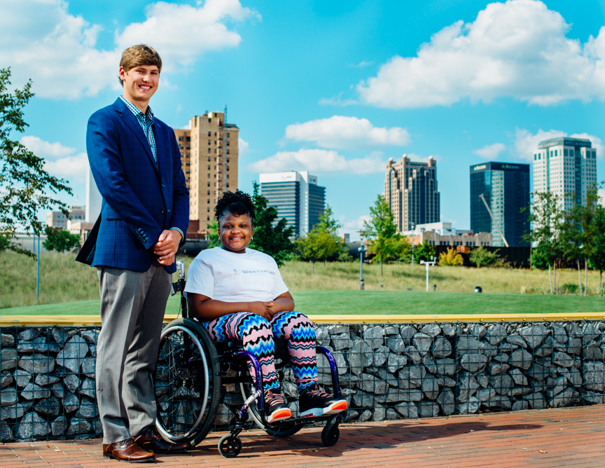 Brennan Peck of Hartbrook Clothier stands with Angel, 14, in Railroad Park in Downtown Birmingham. Men of Magic Moments calendar 2016. (Photo: Andrea Mabry)