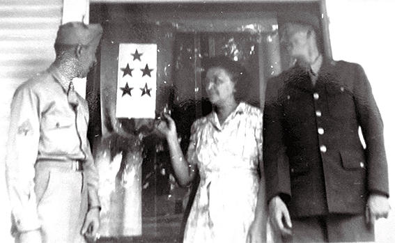 Victoria Tessier touched the five-star flag displayed at the family's West End home during World War II with sons Albert (left) and Louis. While the two men survived the war, they died soon after. Louis, the oldest of the six brothers, had a fatal heart condition. Albert had contracted malaria in the Pacific theater and never recovered. Photo courtesy Hope Tessier.