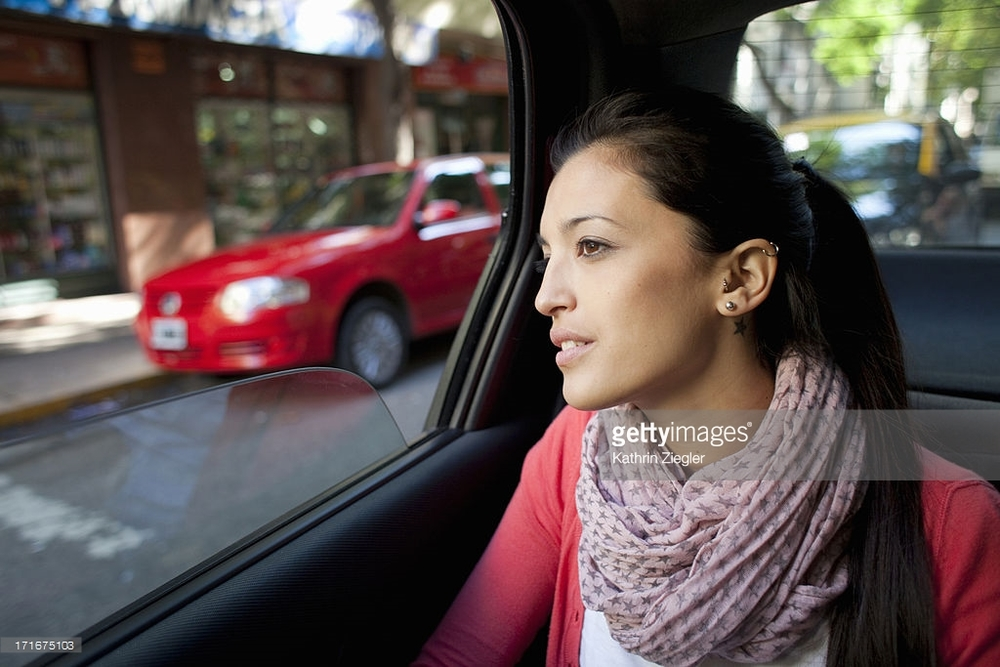 woman-in-the-back-of-a-car-looking-out-the-window-picture-id171675103.jpg