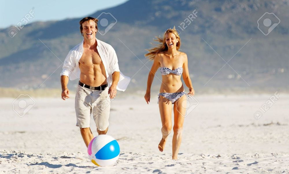 12753599-Summer-beach-couple-playing-with-a-beach-ball-on-the-sand-laughing-and-enjoyng-the-sunshine-outdoors-Stock-Photo.jpg