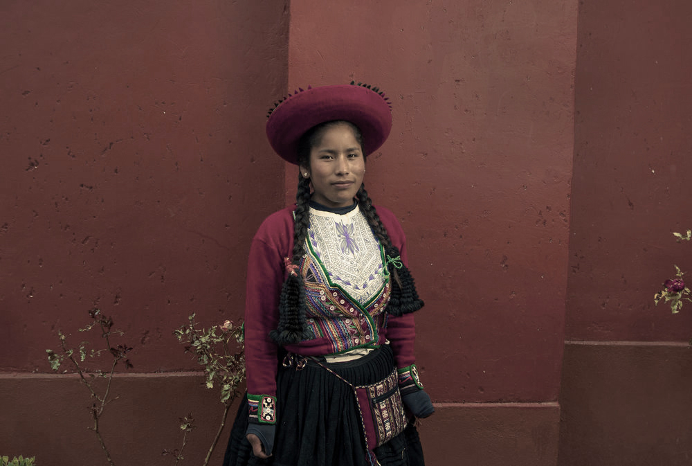 woman in red hat by red wall. puno, peru