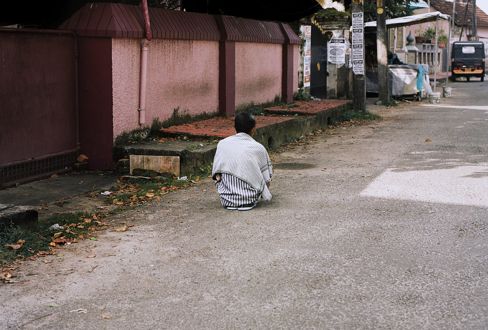 Man meditating in street, Fort Kochi.