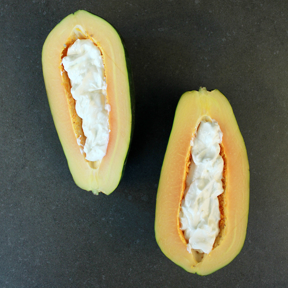 "Scoop yogurt into the papaya ""bowl."""