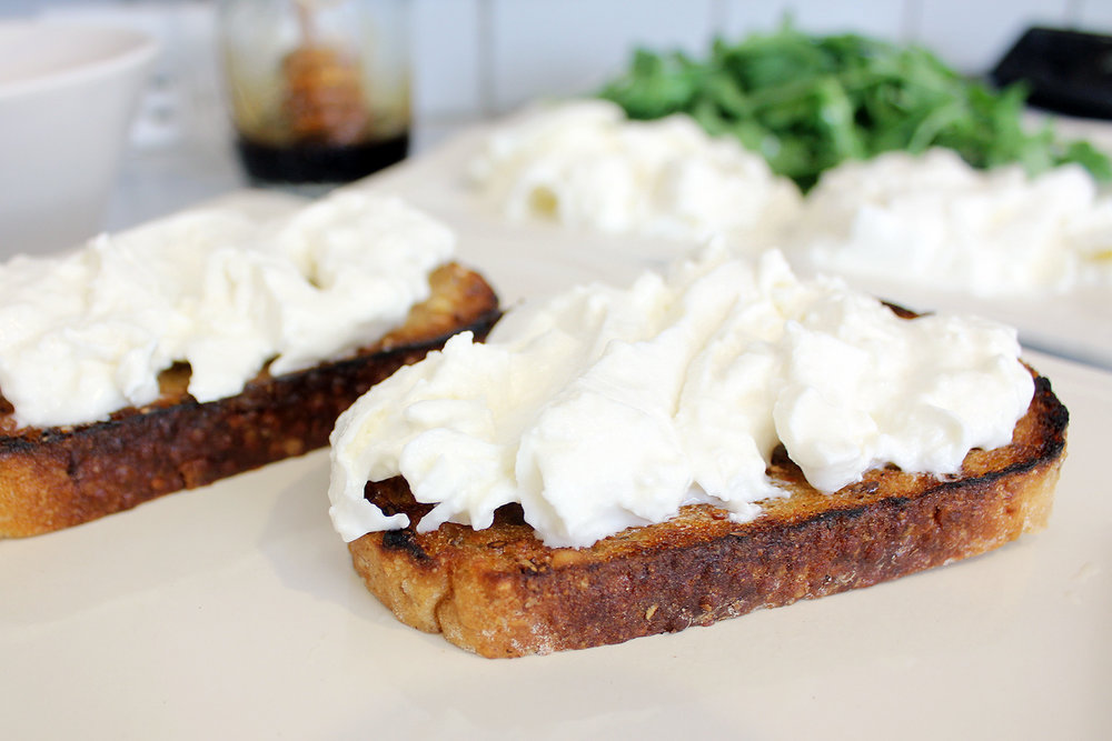 First put a thick layer of burrata cheese on your toasted bread.