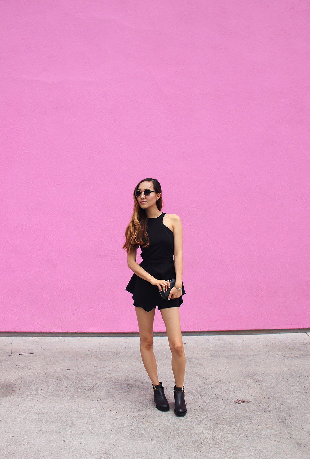 At the pink Paul Smith store wearing a romper by Nasty Gal, booties by Zara, and sunglasses by Urban Outfitters.