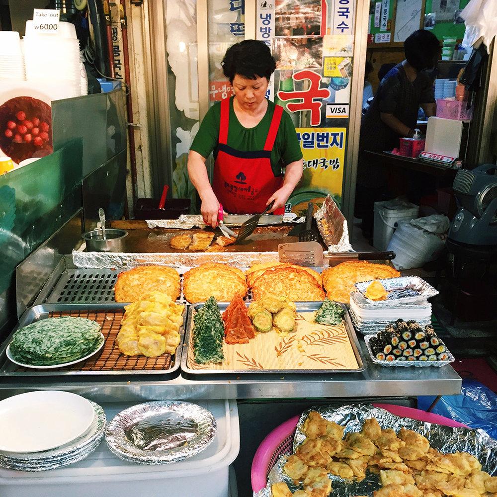 Love watching Korean ajummas working their culinary skills. Here she's making an assortment of fried jeon.