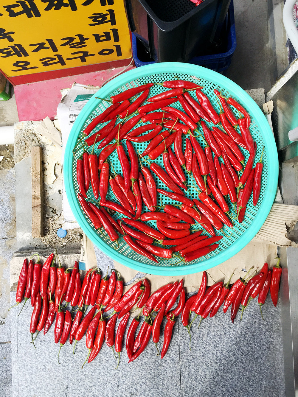 Red chili peppers laying out to dry in the sun. One of the most important ingredients in Korean cuisine, chili peppers are used in a wide variety of dishes, from kimchi, to soups, banchan, and much more! Koreans love spicy food!
