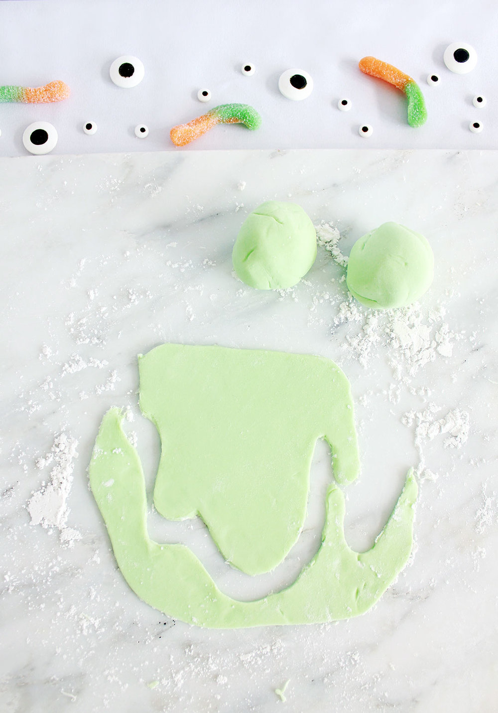 STEP 2 - Add just a dab of green food coloring or icing coloring gel to your fondant. Knead the fondant and add more coloring as needed. Once you're satisfied with your color, separate the fondant into separate little balls (count the number of drinks you will have). Then roll out the fondant and cut out a drip shape. Feel free to play around with the shape. They don't have to all be the exact same size, and they can be long or small drips based on your preference. Once you're done, hang each fondant piece over your glasses and press them onto the glass to keep them in place.