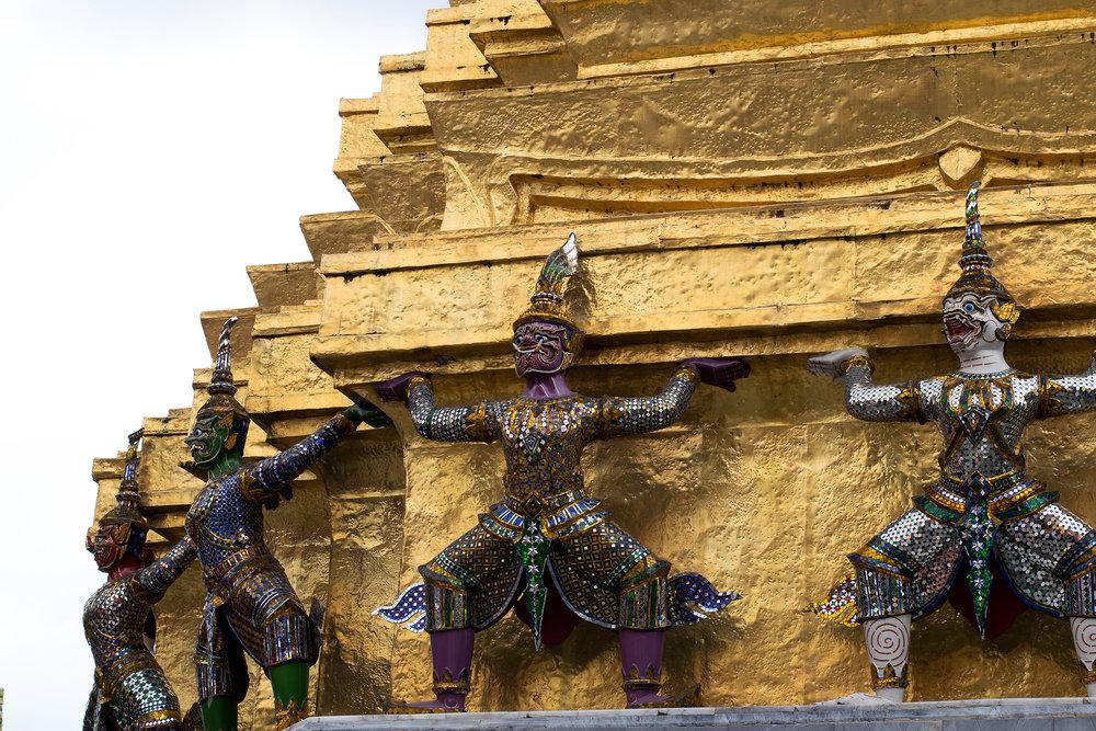 Yaksha demons encircle one of two golden chedis at Wat Phra Kaew.