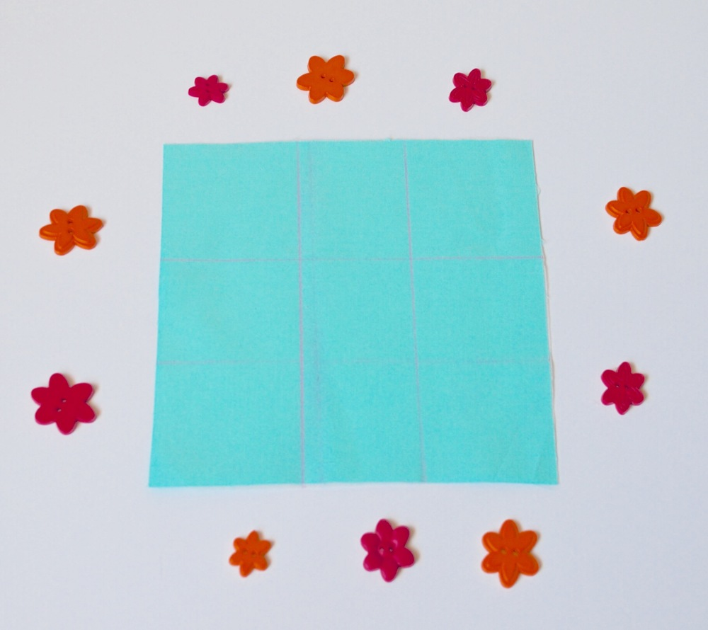 """4. On one 6-3/4"""" x 6-3/4"""" piece of fabric, measure in 2-3/8"""" from the left and right sides and draw a line straight down. Do they same for the horizontal lines."""