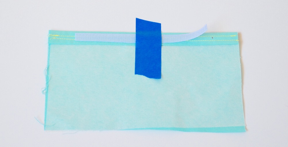 """7. Take out the piece of fabric with the double-fold hem. On the wrong side of fabric center the 5"""" loop tape on the double-fold hem. Tape it down to hold in place instead of using pins (as pins do not go through the hook and loop tape very easily). Sew loop tape on, removing tape as you are sewing."""