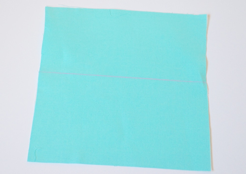 """8. On the remaining 6-3/4"""" x 6-3/4"""" piece of fabric, draw a line 3"""" from the bottom."""