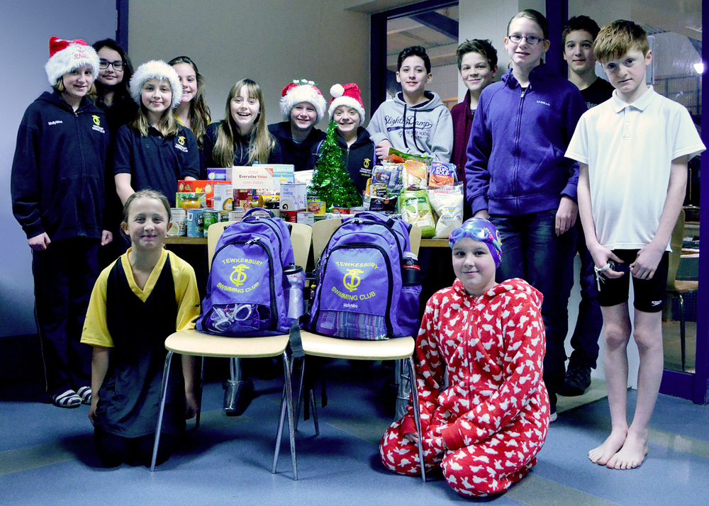 Some of our swimmers proudly presenttheir Foodbank collection