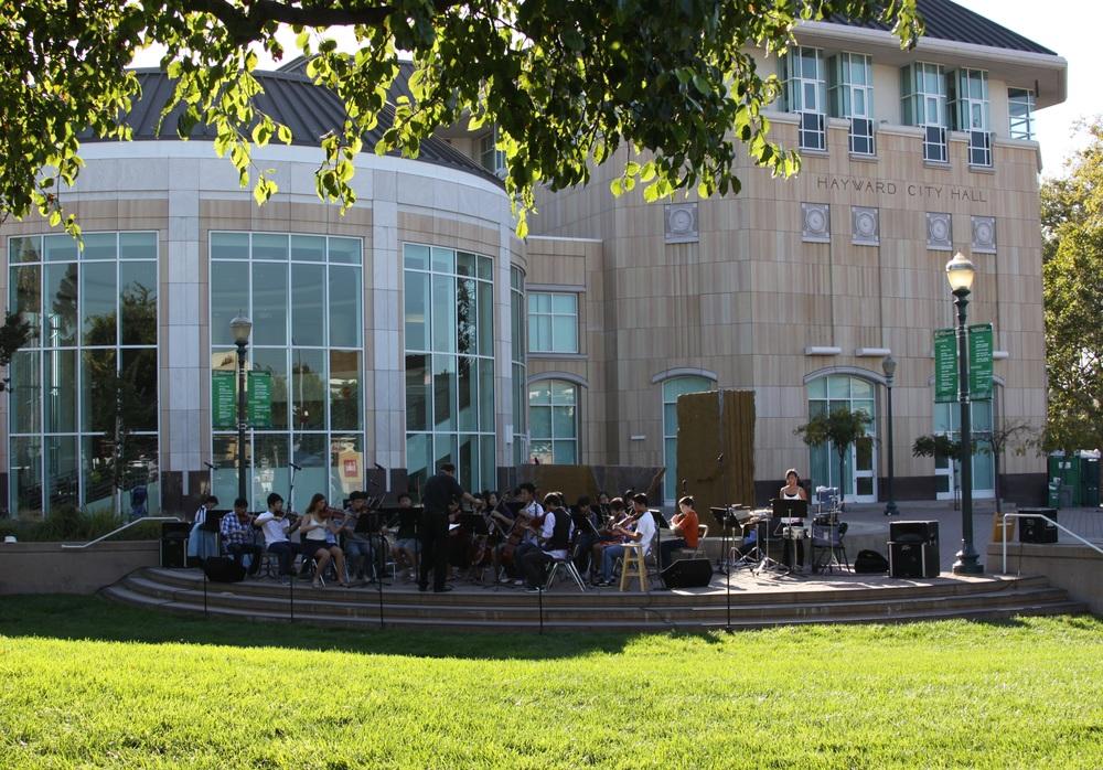 Youth Orchestra Of Southern Alameda Country (YOSAC) performs outdoors at Hayward City Hall. Hayward, California.
