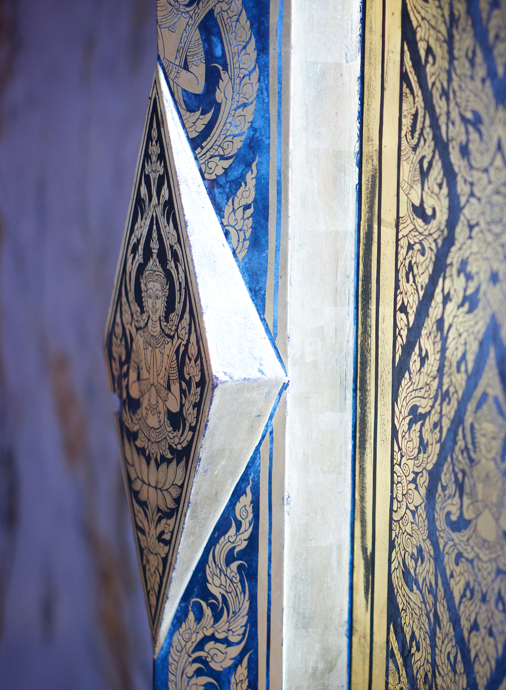 Close-up of a temple door in wonderful city of Chiang Mia. Gold painted on cobalt blue lacquer.
