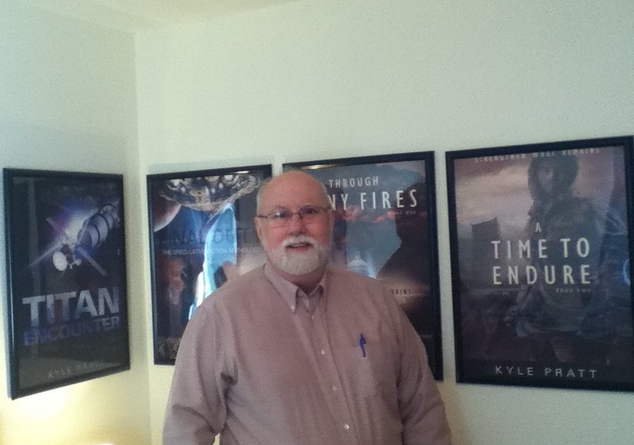 Kyle Pratt with posters of his first four books.