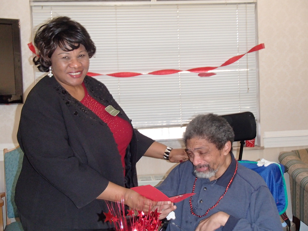 Director of Nursing, Esther Monyei, gives a card to resident Ralph Williams.