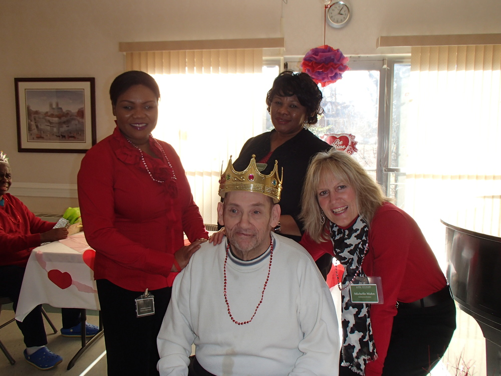Clockwise from left:  Social worker, Jasmine Lacroix, Director of Nursing, Esther Monyei, and Administrator, Michelle Mahn, smile with King Frank!