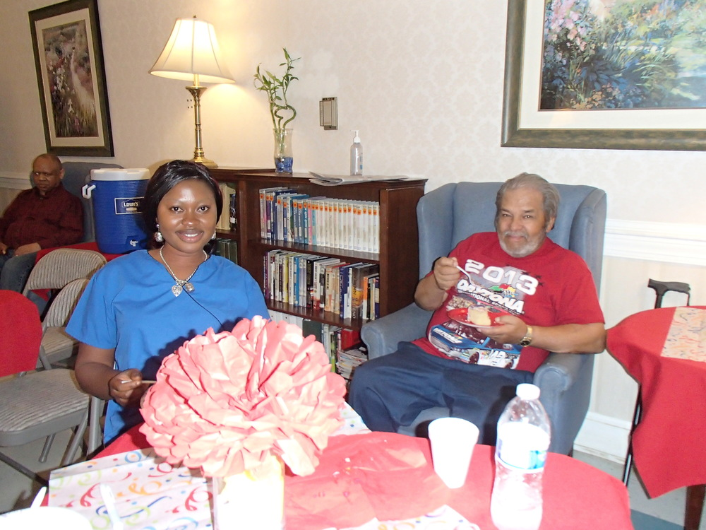 Abibatu enjoying her cake with Mr. Norman Bridgeway