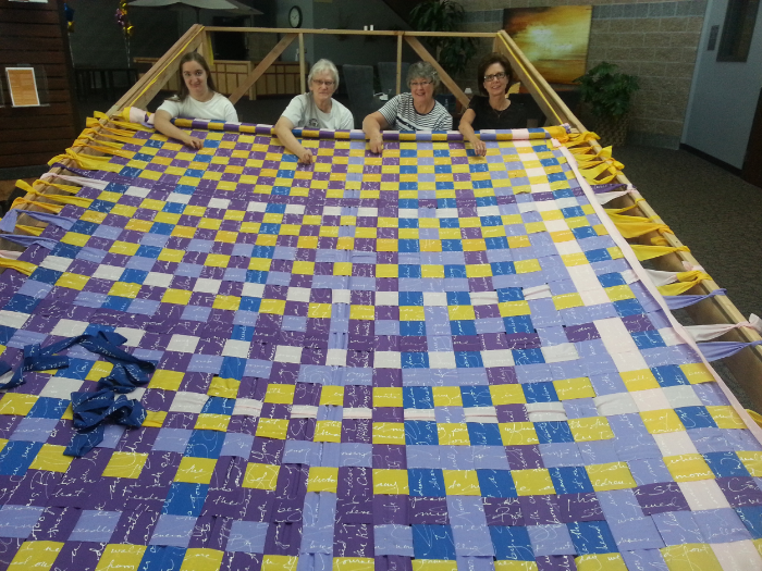 Part of a stitching crew. Each of the three looms could accommodate 4 sewing volunteers at a time. The Navajo-loom-inspired-Olivia-and-Larry-designed warp tightening mechanism worked well for rolling the large pieces and keeping them tight while we worked.
