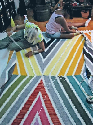 Nicole Byrd, my assistant on the project and myself, hand sewing the diagonal sections to the rest of the rug. I wanted seams without a  bulky ridge,  for the dancers comfort.