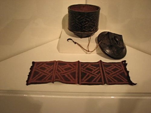 The lidded box is from the Bushoong group, 19th-20th century. The dyed panels are made by the artist Minggshagg of the Ibad clan, Ngeende peoples, Kasai-Mweka region, Mbelo village; 20th century; raffia, resist-dye. 8-3/8 x 24-3/8 in (21.3 x 62 cm).