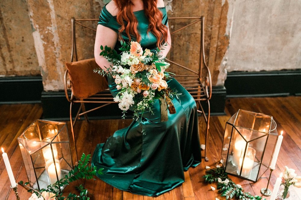 Detail shot of a red headed bride in a unique emerald wedding dress in front of a flower and candle set up inspiration - Bridal Session
