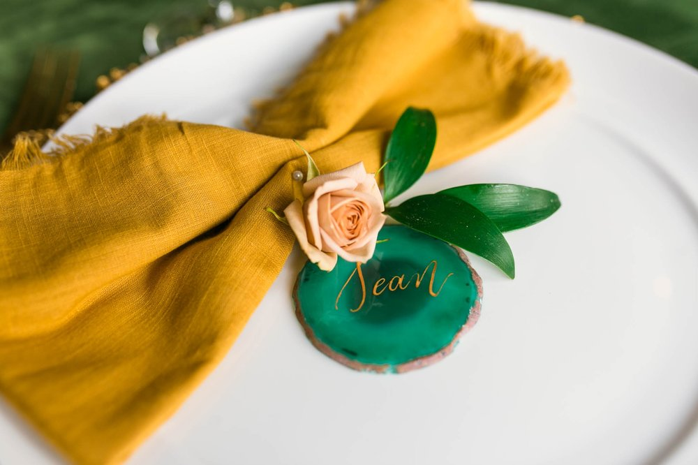 Place setting for a Wedding Guest Table with a Green Velvet Table Cloth, Yellow Napkin and Gold Flatware with Emerald Agate Name Sign and gold calligraphy - oahu hawaii wedding photography