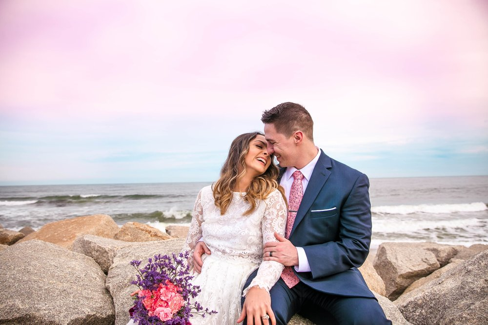 Cotton Candy Sky Beach Elopement Portraits - Bride and Groom sitting on top of rocks Cliffs - - dress by asos with purple and pink flowers and navy suit - oahu hawaii wedding photographer