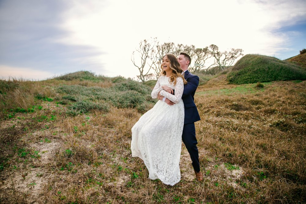 Groom swinging his bride around in Lush Green Grass - Beach Elopement Photography - wedding dress by asos with purple and pink flowers and navy suit - oahu hawaii wedding photographer