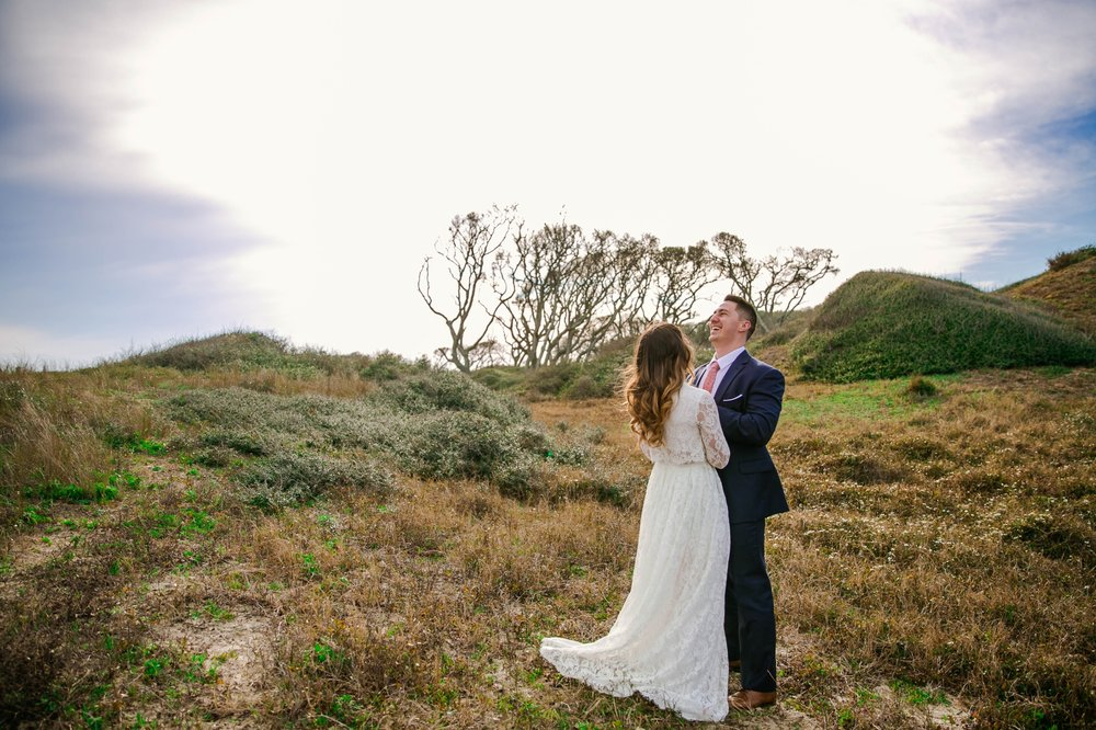 Bride and groom laughing in Lush Green Hills - Beach Elopement Photography - wedding dress by asos with purple and pink flowers and navy suit - oahu hawaii wedding photographer