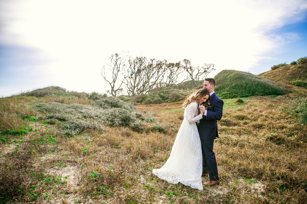 Bride and Groom in Lush Green Hills - Beach Elopement Photography - wedding dress by asos with purple and pink flowers and navy suit - oahu hawaii wedding photographer