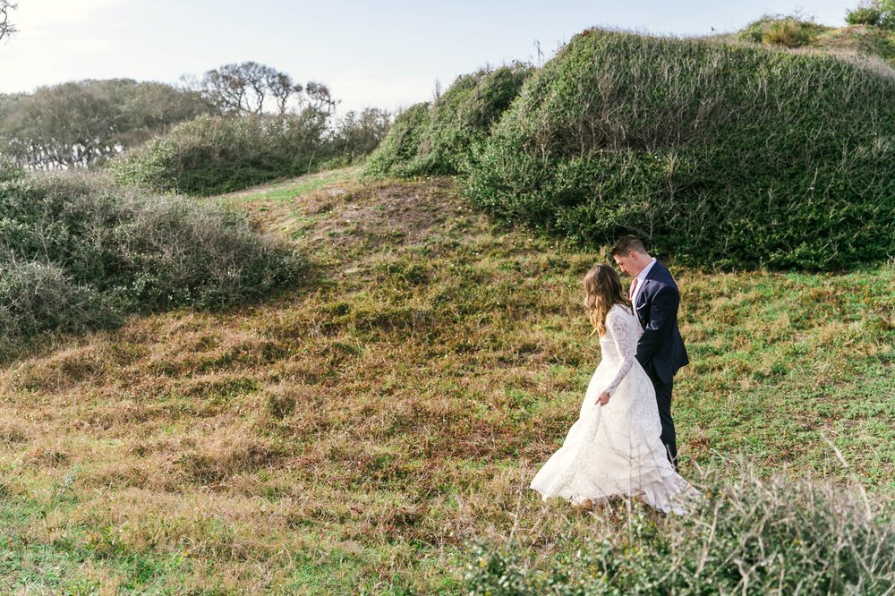 Bride and Groom walking in Lush Green Hills - Beach Elopement Photography - wedding dress by asos with purple and pink flowers and navy suit - oahu hawaii wedding photographer