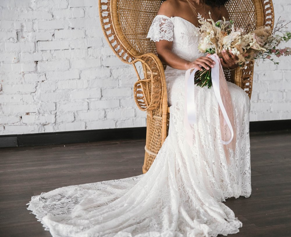 Indoor Wedding Portraits, shot with natural light - black love - african american bride sitting in a Midcentury Woven Wicker Peacock Chair in a boho wedding dress with a big bouquet - tropical inspiration - honolulu, oahu, hawaii photographer