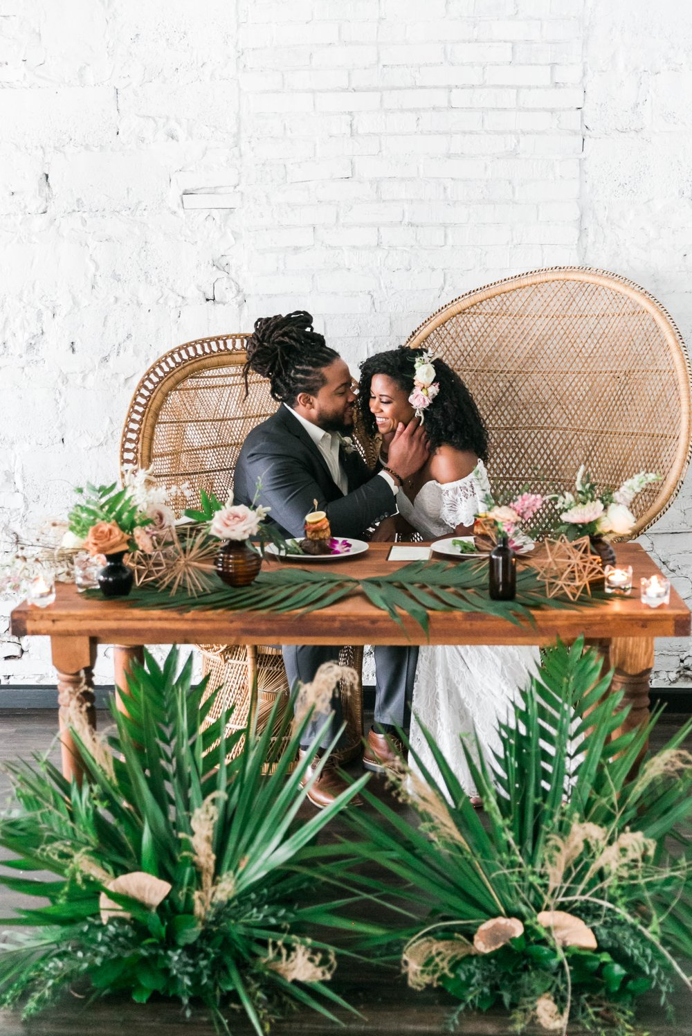 Bride and groom at the sweetheart table at their wedding reception sitting in Midcentury Woven Wicker Peacock Chairs - Black Love - Tropical Destination Wedding Inspiration - Oahu Hawaii Wedding Photography