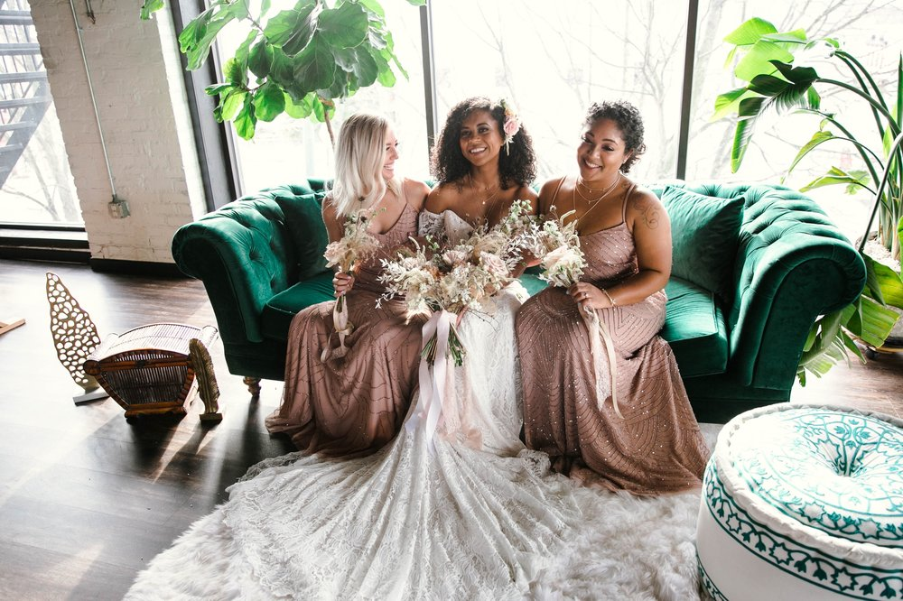 Indoor Natural light portrait of a black bride and her bridesmaids in a boho wedding dress with light pink bridesmaids dresses sitting on an emerald tufted sofa - flowers in natural african american hair - oahu hawaii wedding photographer