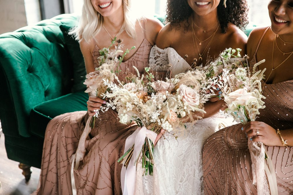 Indoor Natural light portrait of a black bride and her bridesmaids in a boho wedding dress with light pink bridesmaids dresses sitting on an emerald tufted sofa - laughing and having fun with each other- flowers in natural african american hair - oahu hawaii wedding photographer
