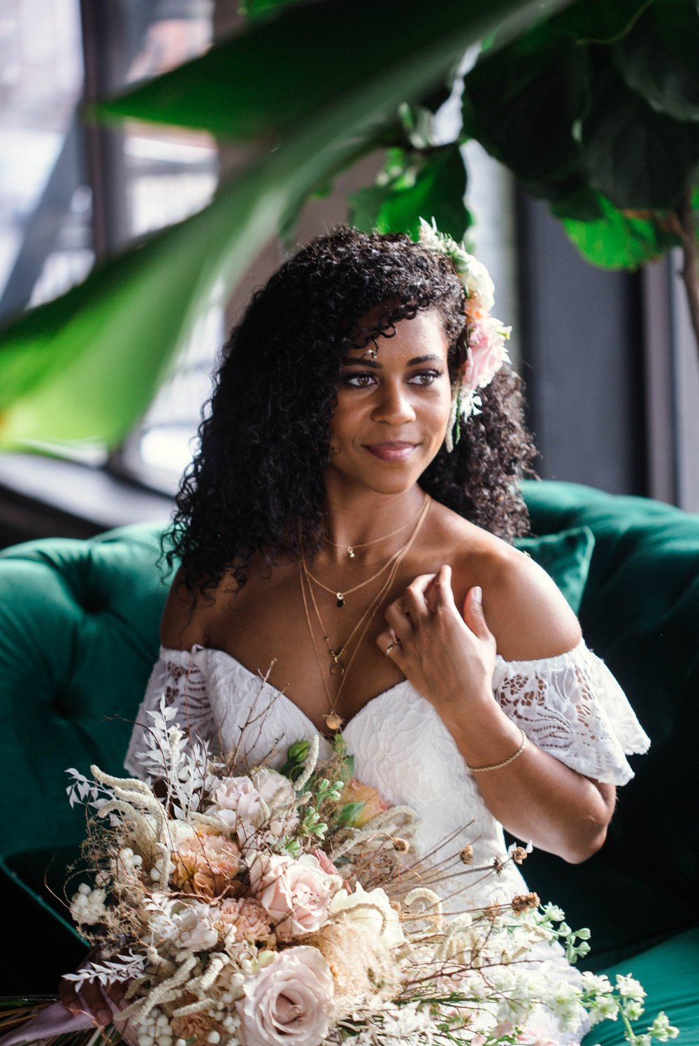 Indoor Natural light portrait of a black bride in a boho wedding dress sitting on an emerald tufted sofa - flowers in natural african american hair - oahu hawaii wedding photographer