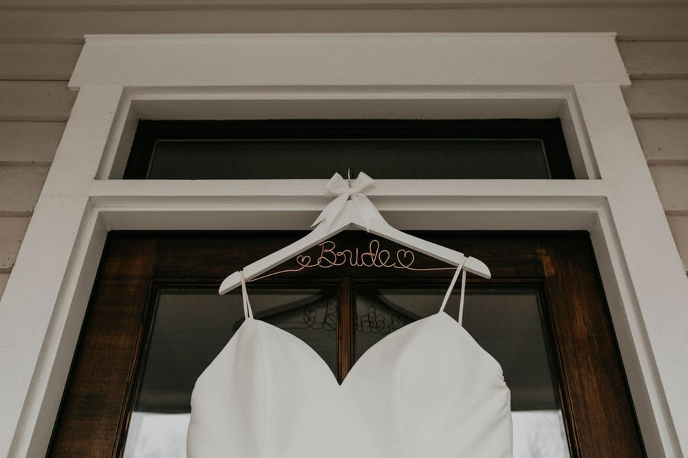 Detail shot of the wedding dress with a white and rose gold hanger that says bride - Matt Smarsh and Johanna Dye - Raleigh North Carolina Urban Edgy Downtown Wedding