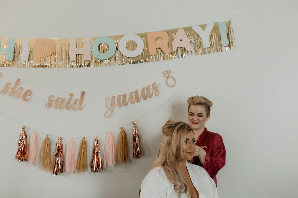 Bride getting her hair done with fun decorations in the background - Matt Smarsh and Johanna Dye - Raleigh North Carolina Urban Edgy Downtown Wedding