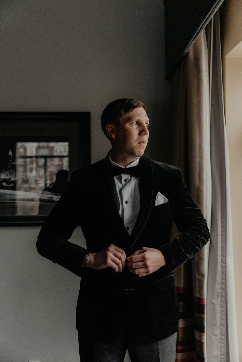 Groom buttoning his suit by the black tux -  Matt Smarsh and Johanna Dye - Raleigh North Carolina Urban Edgy Downtown Wedding