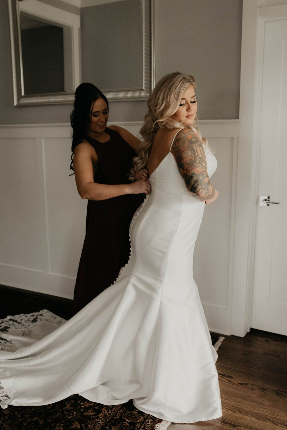 Maid of honor helping the bride getting into her mermaid allure wedding gown - - Matt Smarsh and Johanna Dye - suites by the black tux - Raleigh North Carolina Urban Edgy Downtown Wedding - suits by the black tux